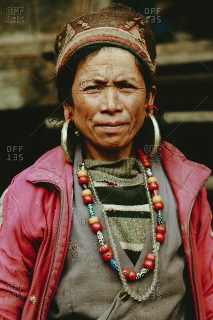 Langtang, Nepal - November 4, 2011: Portrait of a Tamang woman wearing traditional jewelry