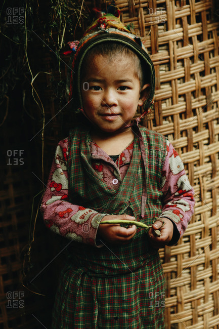 Langtang, Nepal - November 4, 2011: Portrait of a young Tamang girl standing against large woven container
