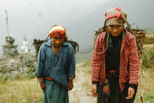 Langtang, Nepal - November 4, 2011: Two Tamang young women carrying baskets on their heads