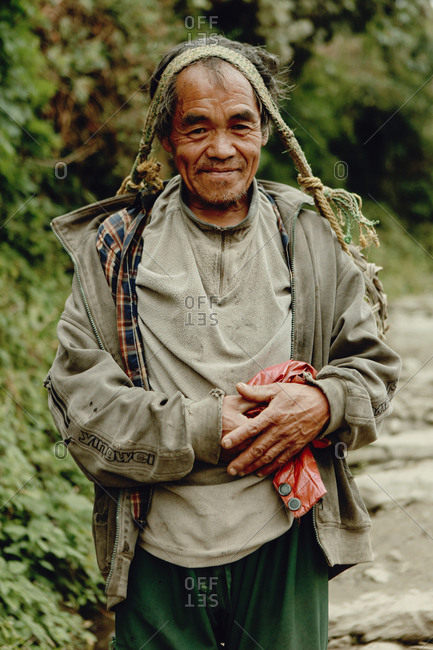 Langtang, Nepal - November 4, 2011: Portrait of Tamang man carrying basket on his head