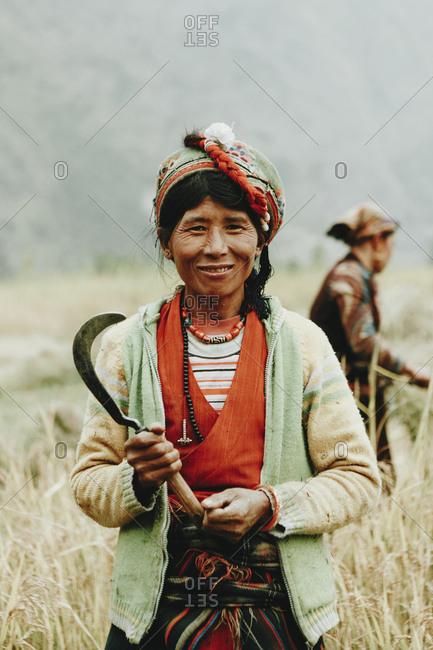 Langtang, Nepal - November 4, 2011: Portrait of a smiling Tamang woman holding a scythe