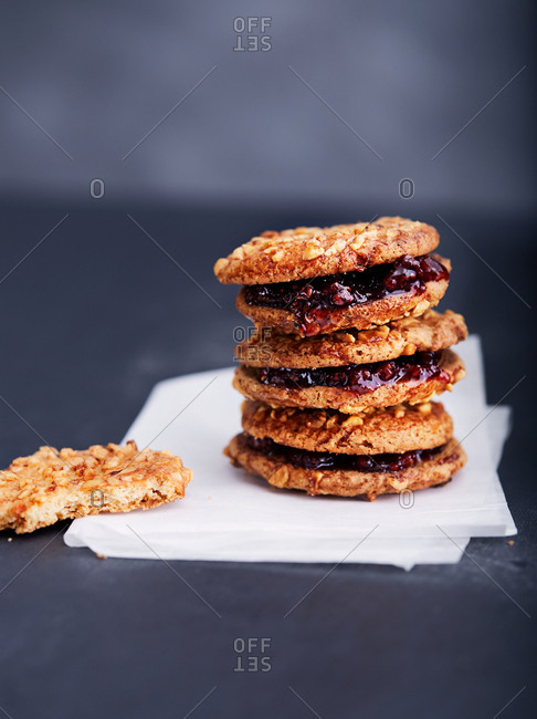 Half eaten cookie next to a stack of irresistible cookies with jam