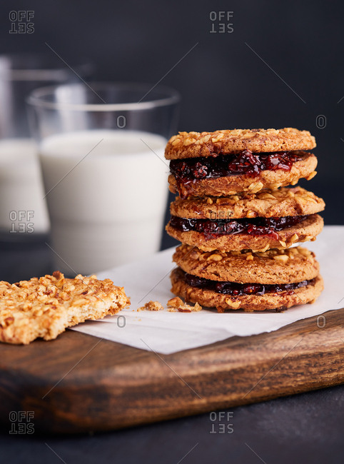 Half eaten cookie next to stack of cookies with jam and glasses of milk
