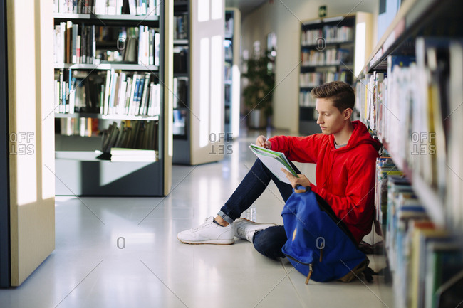 Man studying while sitting on floor at library