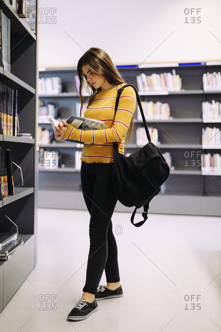 Woman with backpack reading book while standing in library