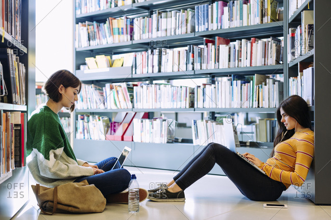 Female friends studying through laptop computers while sitting on floor in library