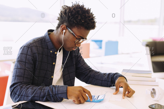 Man with headphones studying while sitting at table in library