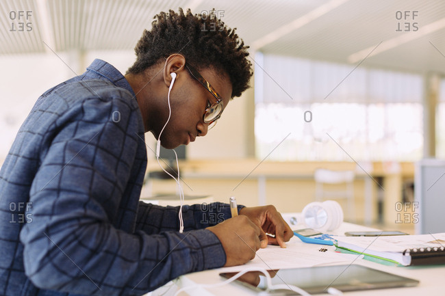 Man with headphones writing while sitting at table in library