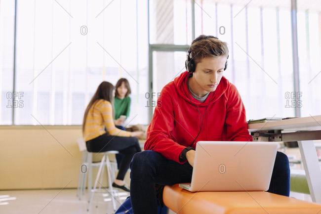 Man using laptop while female friends studying in background at library