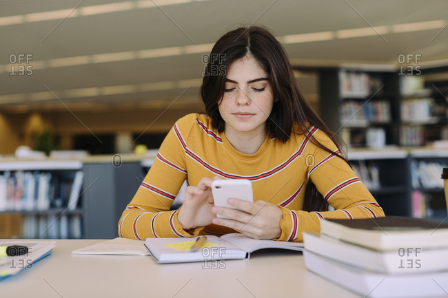Woman using mobile phone while studying in library