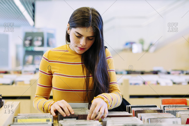 Woman searching book in shelf at library