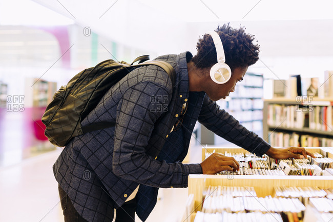 Side view of man searching books in shelf at library