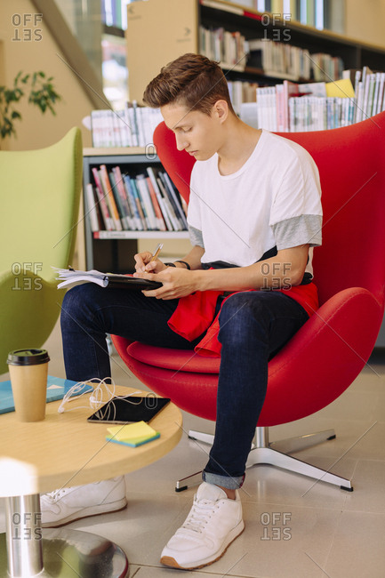 Man writing while sitting on chair in library