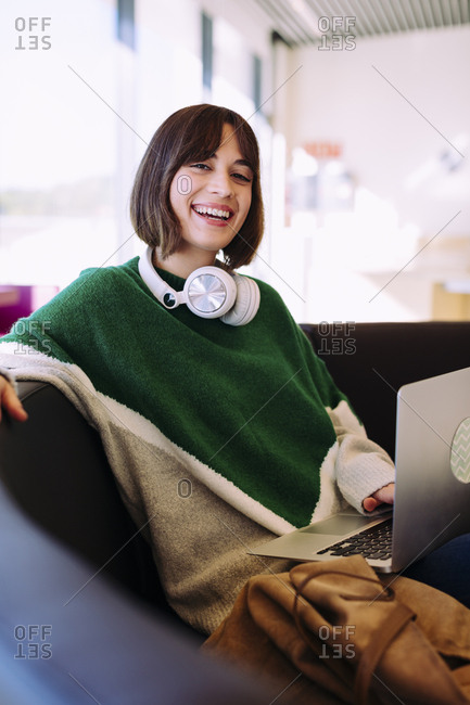 Portrait of smiling woman using laptop computer while sitting on sofa in library