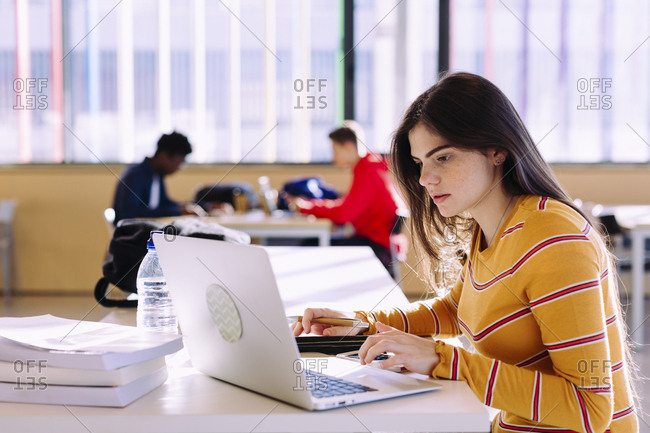 Side view of woman using laptop while male friends studying in background at library
