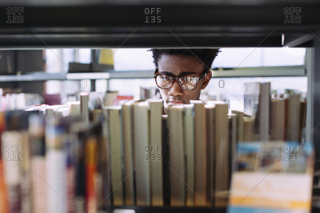 Man searching books in shelf at library
