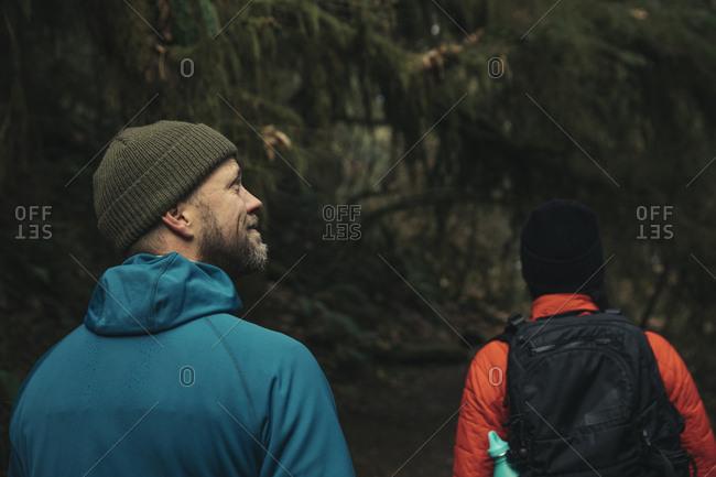 Side view of couple walking on footbridge in forest