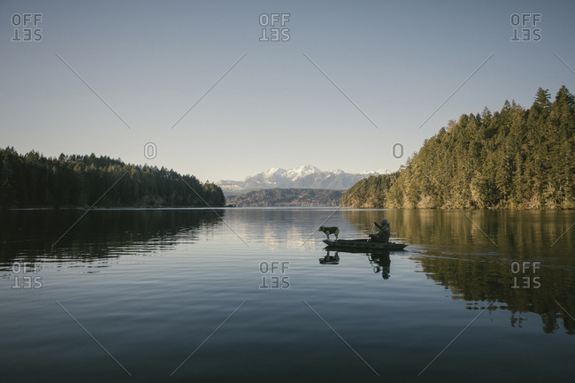Mid distance view of man in boat on lake against sky