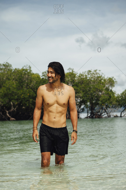 Shirtless cheerful man standing in sea