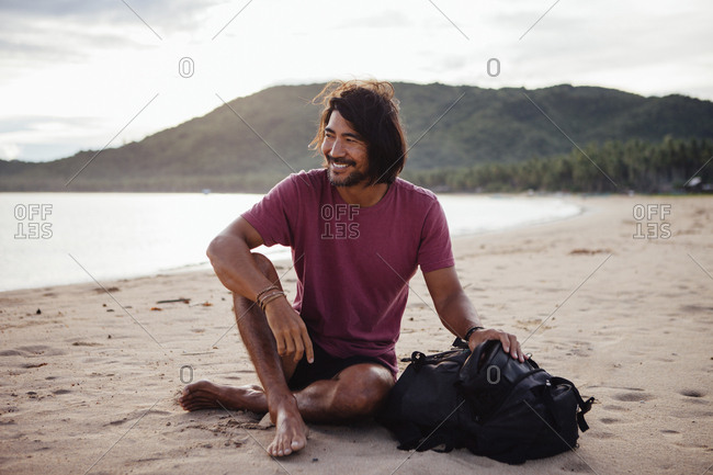 Smiling man with backpack sitting at beach against cloudy sky