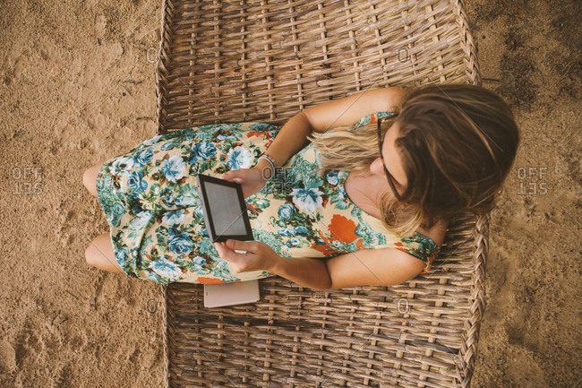 High angle view of woman using tablet computer while relaxing on hammock at beach