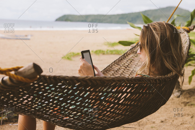 Woman using tablet computer while relaxing on hammock at beach