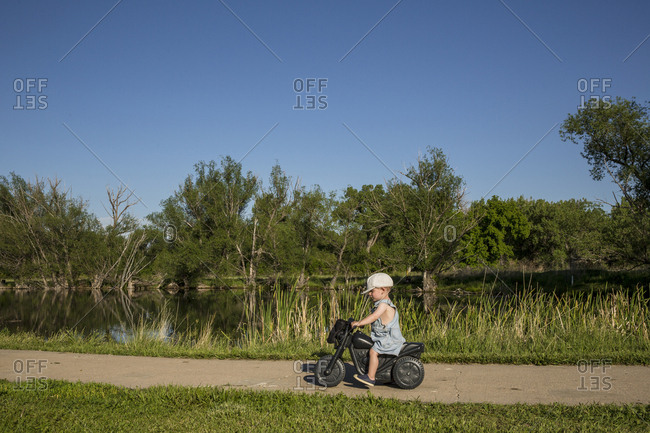Side view of boy riding toy motorcycle by lake at park during sunny day