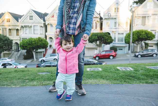 Low section of mother assisting daughter in walking on street