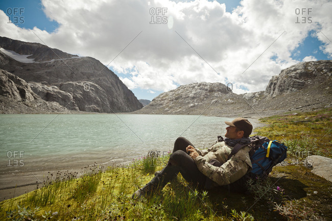 Side view of hiker relaxing at lakeshore during sunny day