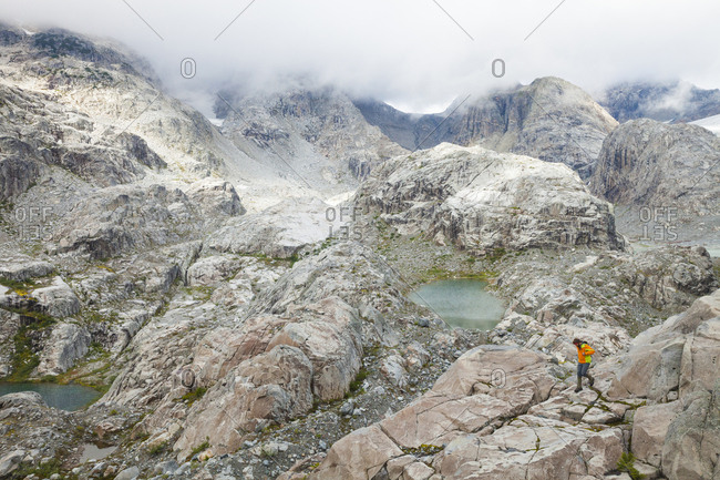 High angle view of hiker walking on mountain during foggy weather