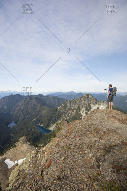 Full length of hiker photographing while standing on cliff against sky