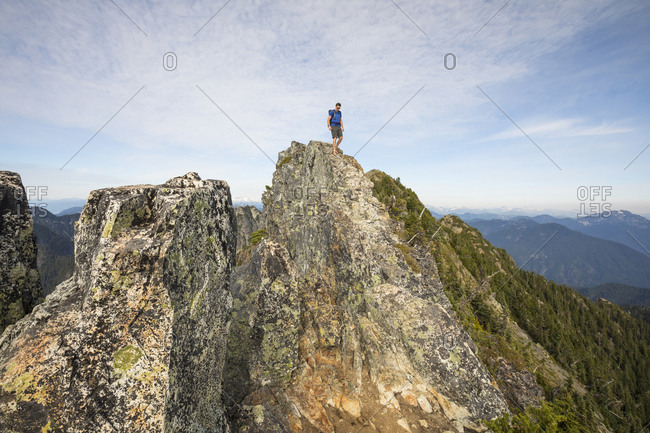 Low angle view of hiker standing on cliff against sky