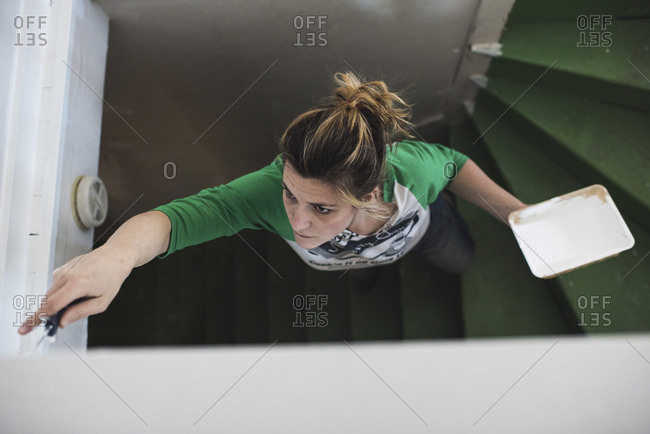 High angle view of woman painting railing while standing on steps at home