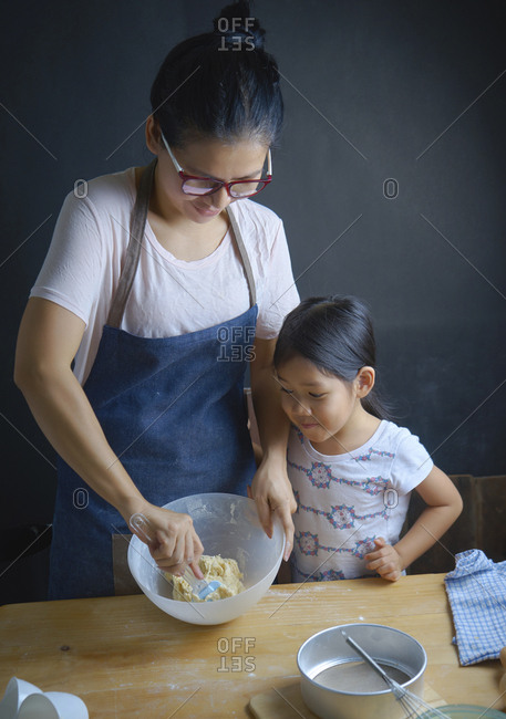 Mother teaching daughter to mix dough in bowl at kitchen