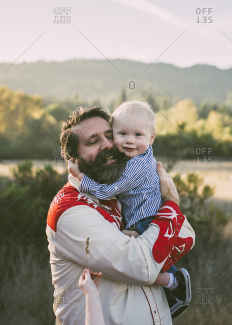 Portrait of cute grandson embracing grandfather at park