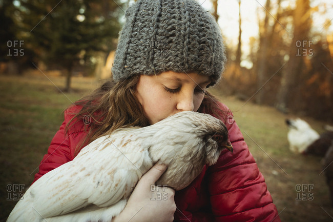 Girl kissing chicken while standing at poultry farm