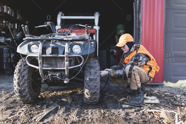 Side view of boy filling quadbike tire with air at fuel station