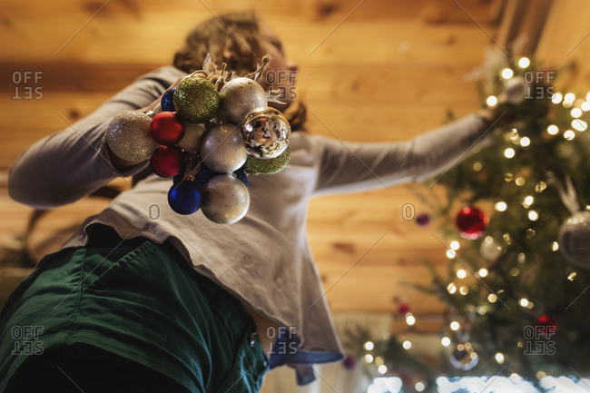 Low angle view of girl decorating Christmas Tree at home