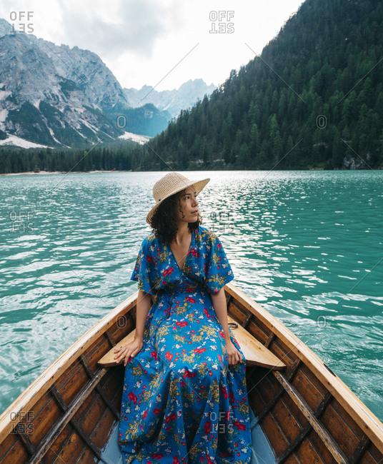 Young woman looking at view while sitting in boat on lake against mountains