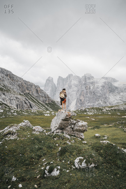Rear view of hiker standing on rock against cloudy sky