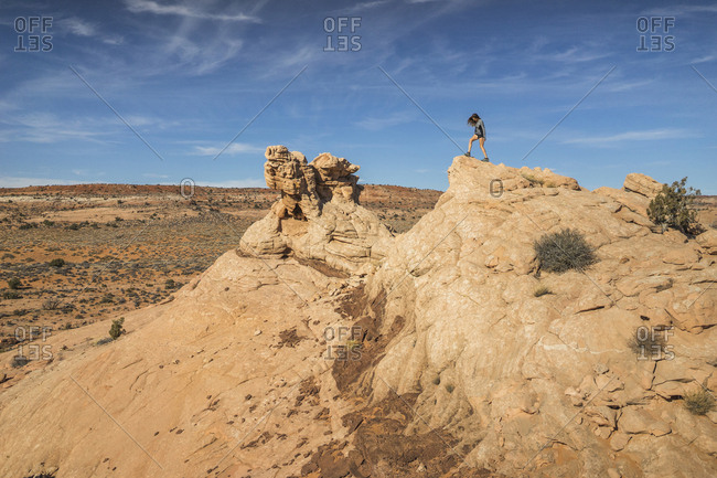 Full length of woman standing on rock formation against sky