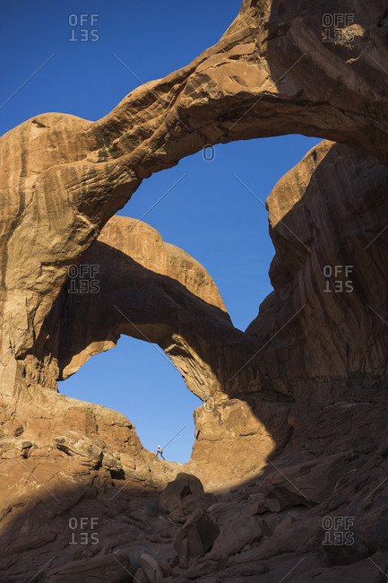 Mid distance view of woman on rock formation at Arches National Park against clear blue sky