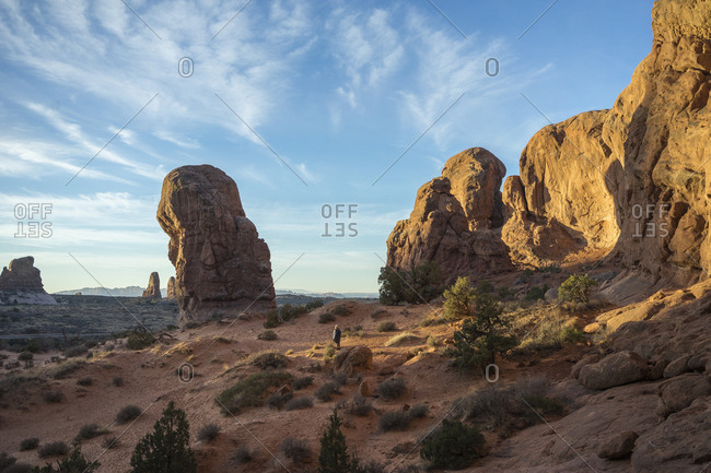 Mid distance view of woman standing on landscape at Arches National Park against sky