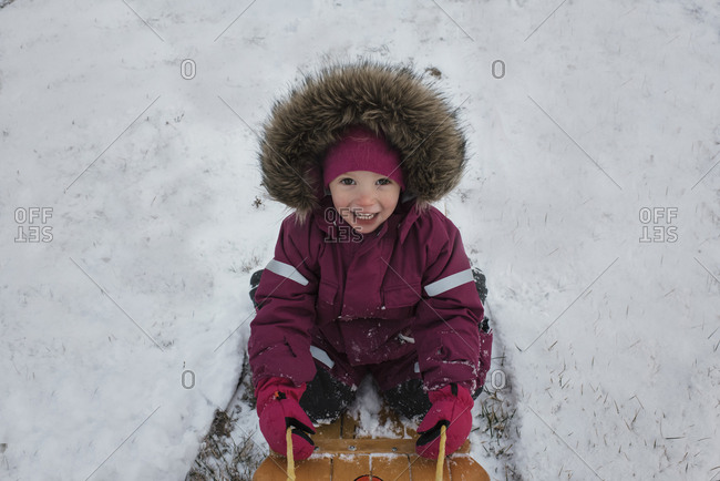 High angle portrait of girl tobogganing on snow covered field