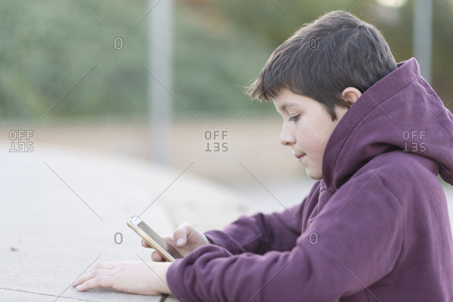 Side view of boy using mobile phone while sitting outdoors