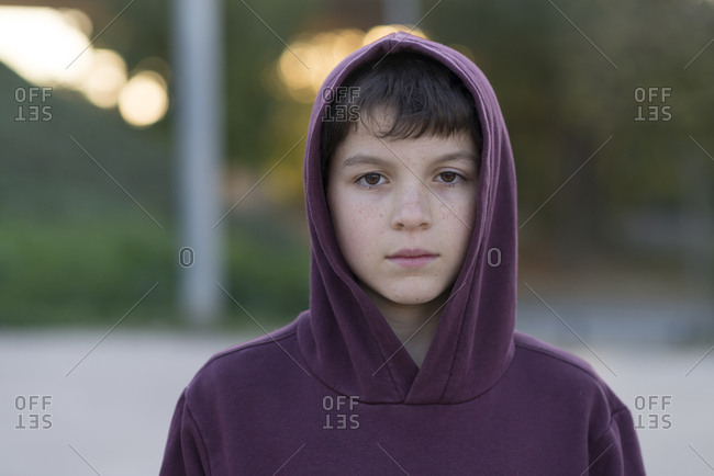 close-up portrait of boy in hooded shirt standing outdoors