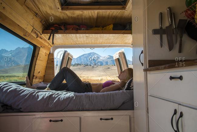 Side view of woman lying on bed in camper van