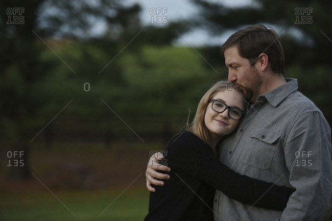 Father kissing daughter while standing at yard