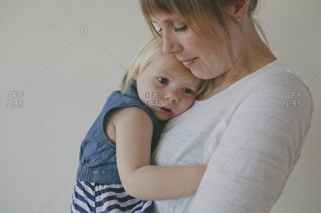 Side view of mother embracing daughter against gray background