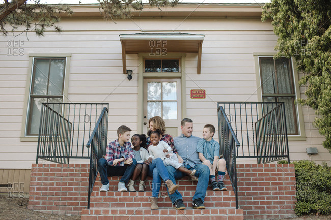 Full length of happy family at sitting on steps at entrance of building